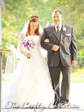 Stefani in her wedding dress being walked down the aisle by her father
