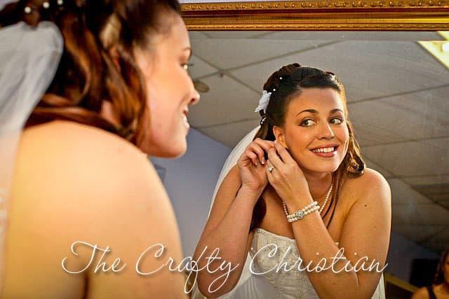 Stefani in her wedding dress putting in an earring