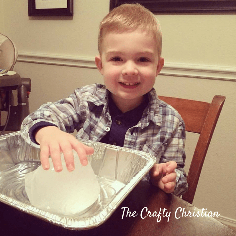 toddler siting a table with one hand on a giant block of ice in a foil tray