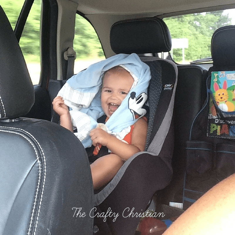 toddler in a car seat being silly