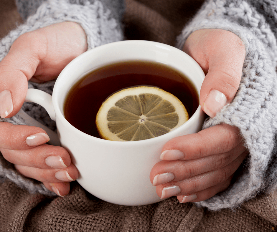 woman's hands holding a tea cup with tea and a lemon slice in it