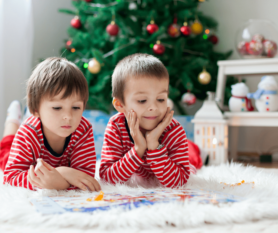 two toddlers in Christmas jammies reading a book on the floor