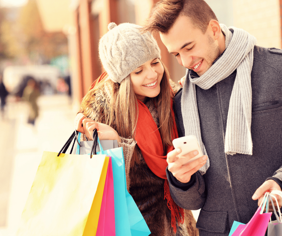 a man and woman in winter clothes shopping and looking at the man's phon