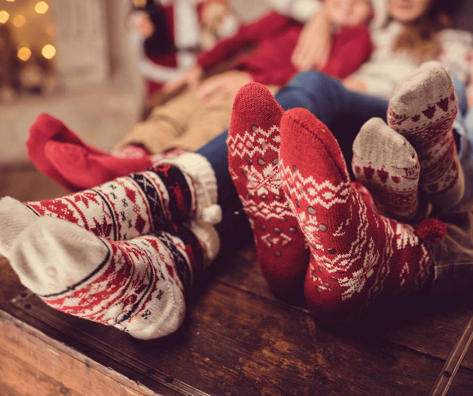 closeup of a family's Christmas socks on a coffee table while they snuggle on a couch