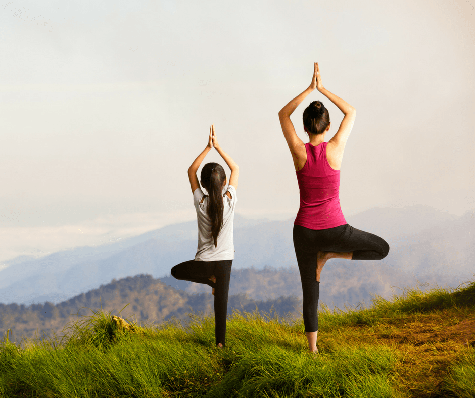 Mom and daughter doing a yoga pose on top of a mountain