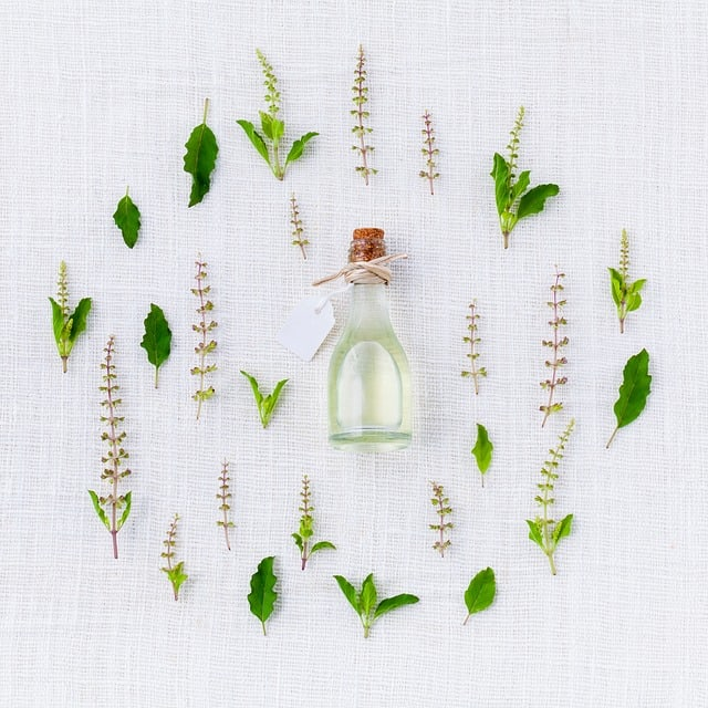 glass bottle in the middle of a bunch of herbs