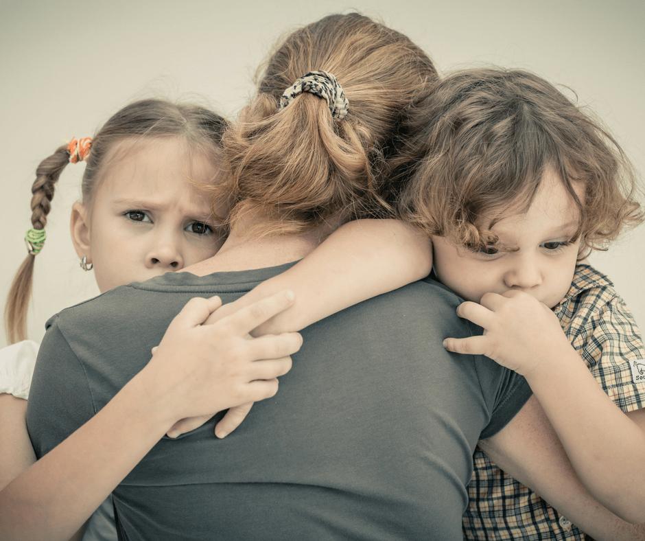 Mom hugging sad girl and boy